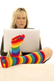 Woman behind laptop serious bright colored socks Royalty Free Stock Images