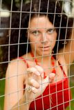 Woman behind a lattice Stock Photography