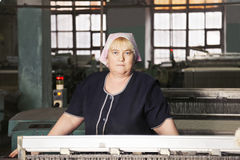 Woman behind the machine at factory Royalty Free Stock Photo