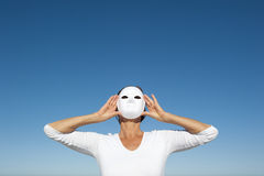 Woman behind mask sky background Stock Image