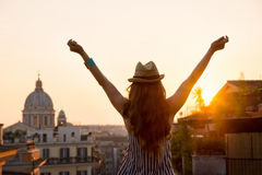 Woman from behind with outstretched arms in Rome at sunset Royalty Free Stock Photography