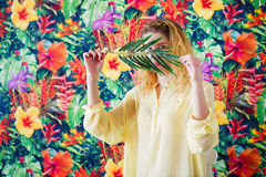 Woman behind palm branch on bright colorful background Royalty Free Stock Photo
