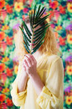 Woman behind palm branch on bright colorful background Royalty Free Stock Photography
