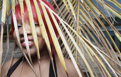 Woman behind a palm frond Royalty Free Stock Images
