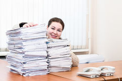 Woman behind pile from blueprints Royalty Free Stock Photo