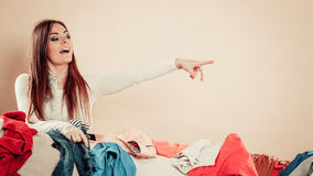 Woman behind sofa full of clothes point with finger. Royalty Free Stock Photography