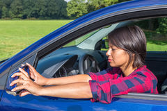 Woman behind steering wheel adjusting car mirror. Colombian woman behind steering wheel adjusting car mirror Stock Photography