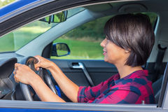 Woman behind steering wheel in car. Colombian woman behind steering wheel in car Stock Photography