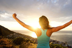 Woman from behind stretching out arms by sunrise. Portrait of woman from behind stretching out her arms in front of sunrise Stock Images