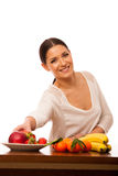 Woman behind the table full of fresh healthy fruit. Royalty Free Stock Images