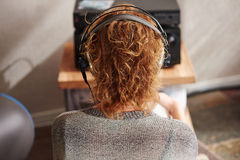 Woman from behind wearing headphones listening to music Royalty Free Stock Photo