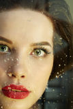 Woman behind wet window Royalty Free Stock Photography