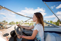 Woman behind the wheel yacht, enjoying nature and river landscape, active sailor girl, female driving luxury water transport, summ Stock Photos