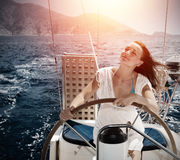 Woman behind the wheel yacht Stock Photos