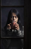 Woman behind window with a cup of coffee or tea Royalty Free Stock Photo