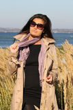 Woman in beige autumn coat posing at beach Stock Photography