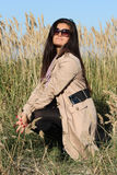 Woman in beige autumn coat sitting outdoors Royalty Free Stock Photo