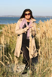 Woman in beige autumn coat standing by the sea Stock Image