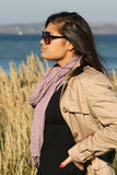 Woman in beige autumn coat standing by the sea Stock Photos