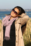 Woman in beige autumn coat standing by the sea Royalty Free Stock Image