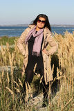 Woman in beige autumn coat standing at seaside Stock Images