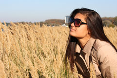 Woman in beige autumn coat and sunglasses Royalty Free Stock Image