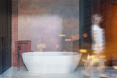 Woman in beige bathroom interior, tub and chair. Woman walking in interior of modern bathroom with beige, black and wooden walls, concrete floor, white bathtub royalty free stock photos