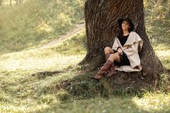 Woman in a beige coat and black hat sitting under tree stock photo