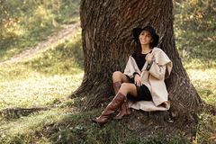 Woman in a beige coat and black hat sitting under tree royalty free stock images