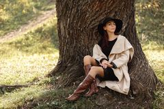 Woman in a beige coat and black hat sitting under tree stock photos