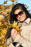 Woman in beige coat with golden leafage. Young beautiful woman in beige autumn coat with golden leafage Royalty Free Stock Images