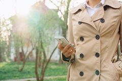 Woman in beige coat holding a mobile phone Stock Images