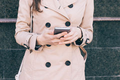 Woman in a beige coat holds a mobile phone in hands Royalty Free Stock Photography