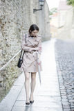 Woman at beige coat look at pale hand Stock Images
