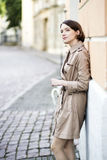 Woman at beige coat observe actions on street Stock Photo