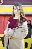 Woman in beige coat and red dress Stock Photos