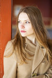 Woman in beige coat with sad face Stock Photo