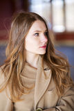 Woman in beige coat with suprise look. Young woman in beige coat with suprise look Stock Images