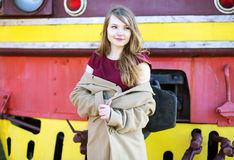 Woman in beige coat before train front Royalty Free Stock Photo