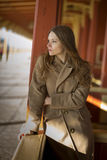 Woman in beige coat waiting her train Stock Photography