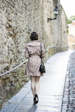 Woman at beige coat walks along the wall Stock Photo