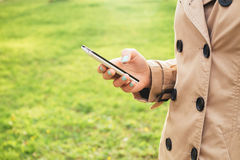Woman in beige coat walks in the park and enjoy a smartphone Royalty Free Stock Photo