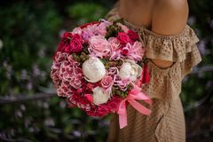 Woman in beige dress holding a romantic bouquet of flowers in pink tones stock photo