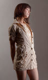 Woman in Beige Dress With Lace. An image of a young woman in a pretty, fashionable outfit with buttons and lace Royalty Free Stock Image
