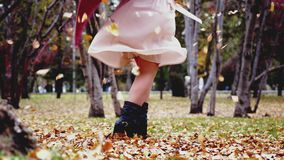 Woman in a beige dress throwing leaves in an autumn fall park having fun in slow motion. View of her legs. 3840x2160 stock video footage