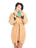 Woman in beige fall coat with green scarf Stock Images