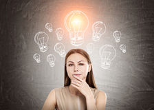 Woman in beige and light bulb, blackboard Stock Photography