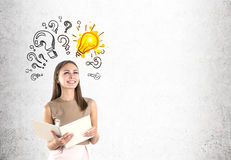 Woman in beige, light bulb and questions Royalty Free Stock Photo