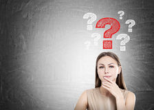 Woman in beige and question marks, blackboard Stock Photo