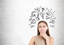 Woman in beige and question marks, concrete Royalty Free Stock Image